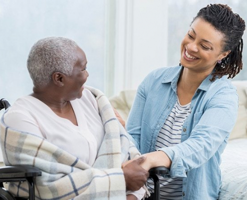 A smiling Family Caregiver looking at their aging parent.